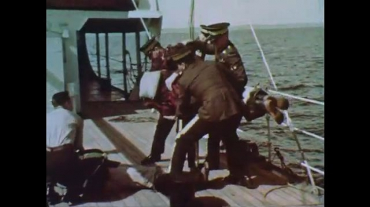 1960s: Officers pull man to safety and lay him on deck.  Man smiles.  Boat arrives.  Man in stretcher.  Men speak and shake hands.