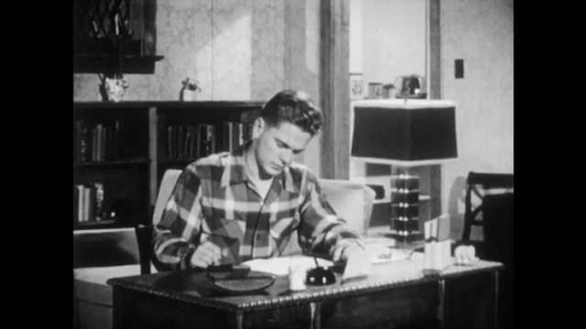 1950s: Boy at desk, stands, looks through book. Text on page, light illuminates portion.