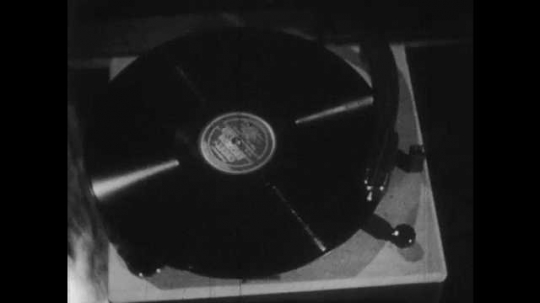 1950s: Record turns on record player. Houses in various architectural styles. Man mixes liquids in chemistry lab.