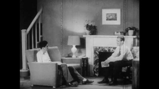 1950s: Man stands up from chair, talks to teenager sitting on couch. Teen boy sits on couch, talks.