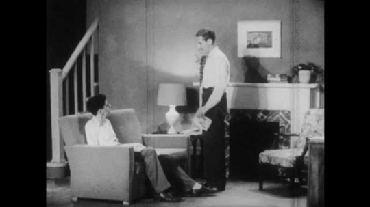 1950s: Man talks to teenager sitting on couch. Teen boy sits on couch, talks.