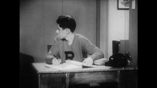 1950s: Boy sits at desk, pen in hand, thinks.