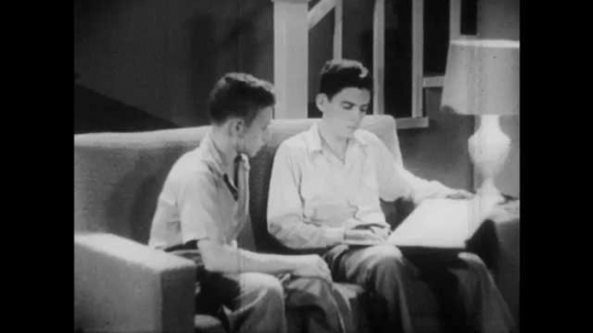 1950s: Two boys sit on couch, look at book, boy points at book, boy looks thoughtful. Boy sits at desk, thinks, picks up book, looks at book.