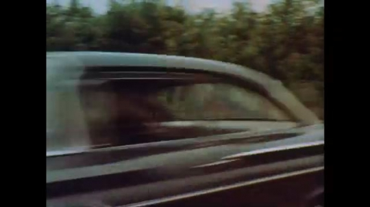 1960s: Car speeds down road.  Police barricade.  Man holds up hands to stop.  Car stops and driver tries to run.  Officer captures man.  Officer jumps fence to chase suspect.