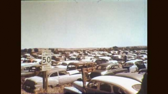 1960s: Car junkyard full of rusting cars. Cluster of advertising signs. Chicago skyline. School bus passes litter up against chain-link fence