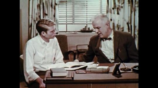 1960s: UNITED STATES: Two men speak in office. Student talks with teacher. Man writes down notes at desk.
