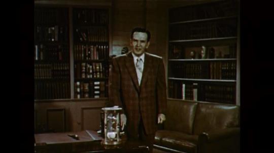 1950s: UNITED STATES: man speaks to camera. Egg timer. Hand turns sand timer upside down
