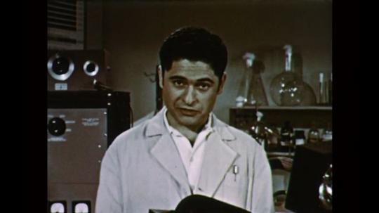 1950s: UNITED STATES: man in lab coat speaks to camera. Hands on recording device. Men in lab. Men speak
