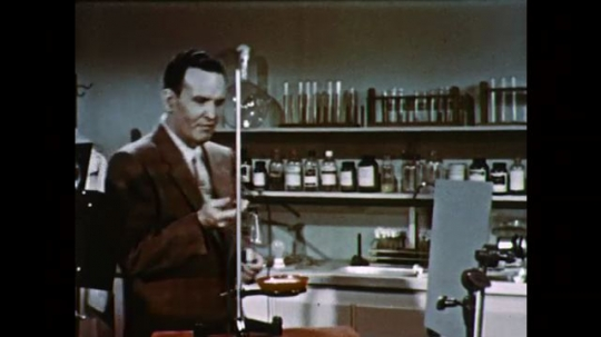 1950s: UNITED STATES: man in science laboratory speaks to camera. Man drops object