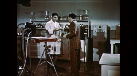 1950s: UNITED STATES: two men experiment in laboratory. Man puts egg on head. Man with bow and arrow