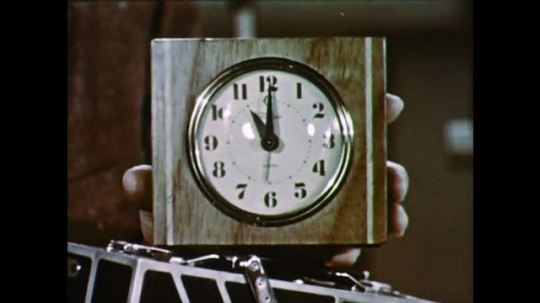1950s: UNITED STATES: hand holds clock. Clock shows eleven. Man puts clock on table