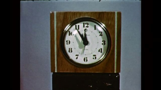 1950s: UNITED STATES: speeding hands on clock face. Man speaks to camera.