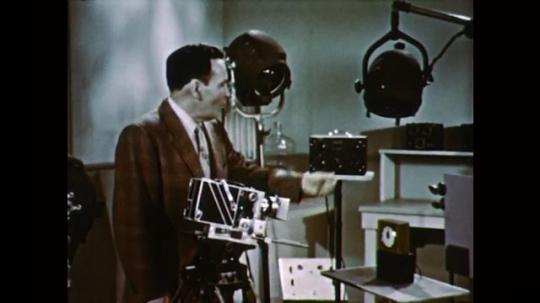 1950s: UNITED STATES: man speaks to camera. Man turns on flashing lights.