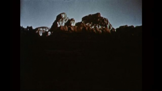 1950s: UNITED STATES: sun moves across mountain landscape. Time lapse clouds over mountains. Clouds in sky