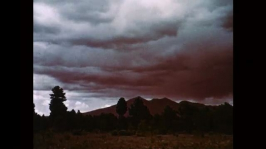 1950s: UNITED STATES: time lapse clouds move mountain and valley. Mist on mountains. Clouds roll through valley