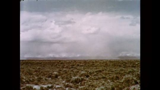 1950s: UNITED STATES: time lapse clouds move across landscape and mountains.