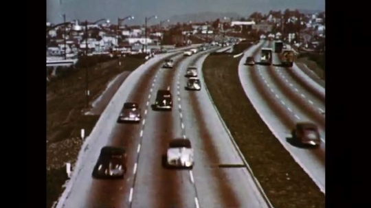 1950s: UNITED STATES: time lapse of cars on road. Speeded up cars on road. Car drives through city. Cars pull up by lights