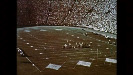 1950s: UNITED STATES: speeded up players in stadium. People leave stadium.