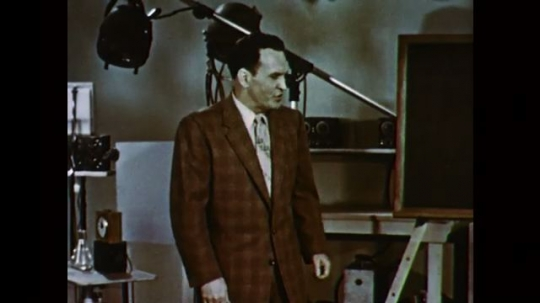 1950s: UNITED STATES: man speaks to camera. Man stands by chalk board.
