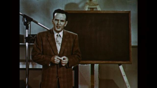 1950s: UNITED STATES: man speaks to camera. Man stands by chalk board. Man writes on chalk board. Science equation
