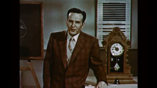 1950s: UNITED STATES: man speaks to camera in suit. Man stands by clock. Man writes on chalk board.