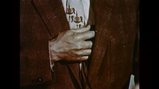 1950s: UNITED STATES: man stands with hand over heart. Man moves pendulum on clock. Close up of clock pendulum