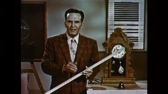 1950s: UNITED STATES: man in suit holds long ruler in hands. Man speaks to camera. Clock pendulum swings.