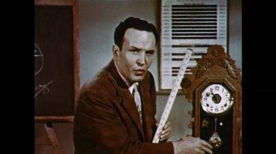 1950s: UNITED STATES: man stops clock pendulum moving. Man speaks to camera. Man holds metre stick.