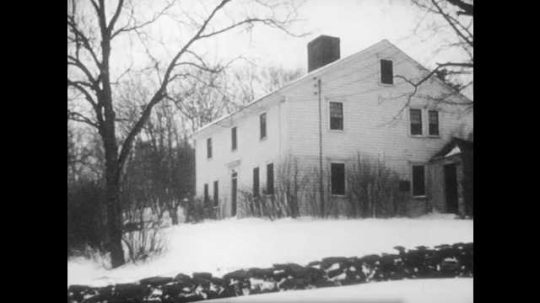 1950s: A farmhouse stands in the snow, the childhood home of John Greenleaf Whittier. Inside, a fire burns in the fireplace. A rocking chair and spinning wheel stand nearby. Snow falls outside.