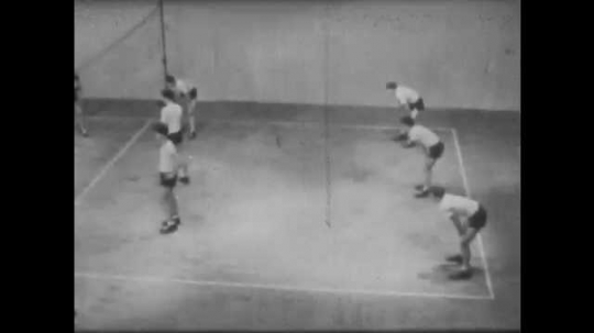 1940s: Male volleyball players change position and rotate. Boy serves ball, match continues.