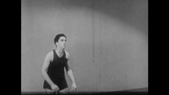 1940s: Boy hits the ball with hands above the chest. Volleyball match.