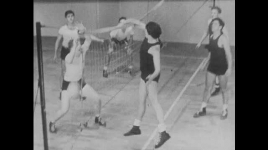 1940s: Volleyball player touches net. Volleyball team practices and spikes the ball.