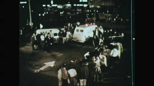 1960s: Vehicle parked. Person opens vehicle doors. People look. Paramedics roll out stretchers
