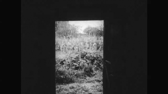 1950s: Two boys are caught in the rain, take shelter in a barn. Rain falls. The boys shake off water from their hands and talk. The boys look at the rain and wait.
