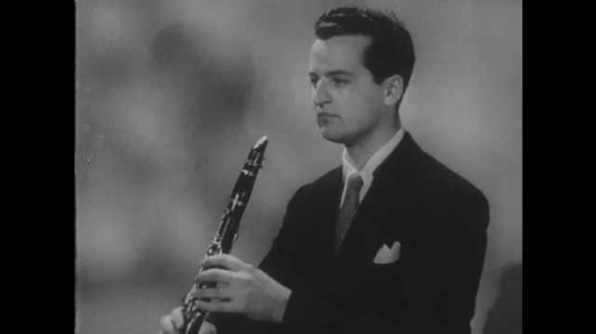 1950s: Man plays clarinet. Man pulls mouthpiece off clarinet and blows into it.