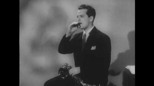 1950s: Man puts mouthpiece on alto saxophone. Man plays saxophone.  Table with sheet music.