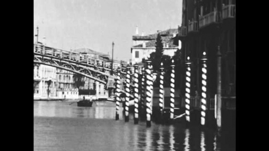 1950s: Bridge and poles built in water. Double story buildings. Men row boat.  Children clean boat, Boats move in narrow water way surrounded by buildings