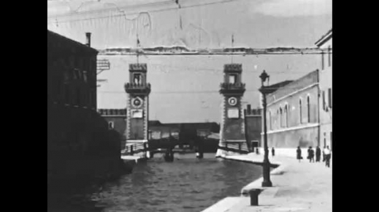 1950s: Waterway lined with buildings. Detailed building with statues and flag on top.