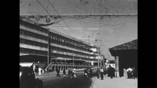 1950s: Building on street. People walk on street. Gondola approaches bridge