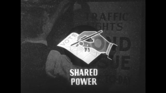 1950s: Illustration of hand voting superimposed over man hanging poster. Hands count voting slips. View of intersection.
