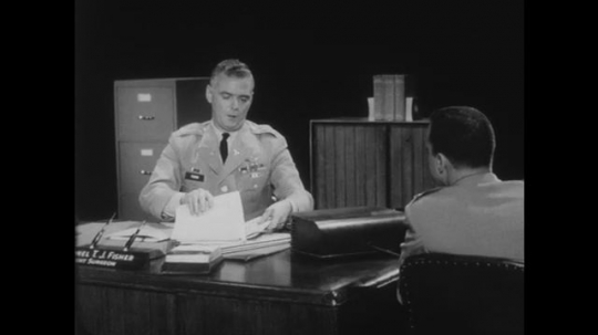 1950s: Two men in military uniforms sit at a desk and talk. Man behind desk opens a file folder.
