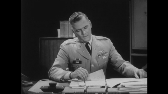 1950s: Man in military uniform sits at desk and talks. Man on other side of desk looks concerned. Man reads from paper inside file.