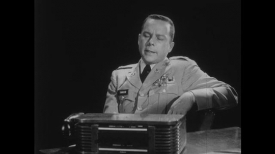 1950s: Man in uniform sits in chair and talks. Man in uniform sits behind desk and talks.