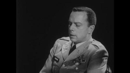 1950s: Man in uniform sits in chair, talks. Man in uniform sits behind desk, nods head, talks.