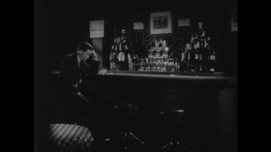 1950s: Man sits alone at a bar, looks sad. Man approaches man and reaches out hand. Man turns away from shaking hands. Man sits down at table. Man drinks alcohol and orders another drink.