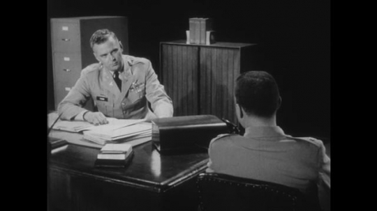 1950s: Two men in military uniform sit in an office and talk. Man behind desk closes file folder, leans forward, talks, taps folder with finger.