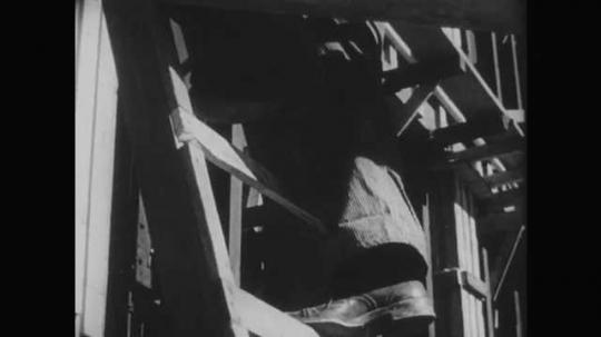 1950s: Man steps back down ladder and checks cracked step.