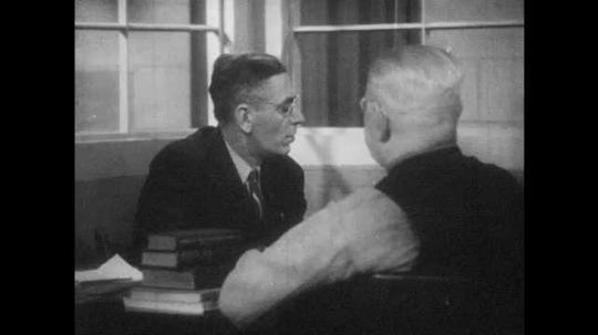 1940s: Men sit in office, talk. Man sniffs sandwich, throws it away.