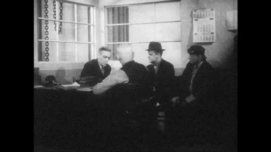 1940s: Men sit in office, talk. Men get up and leave, man sits at desk, writes.