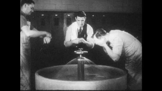 1940s: Men wash up at large sink in locker room. Man walks to locker, puts on coat, walks through factory. Factory buildings.